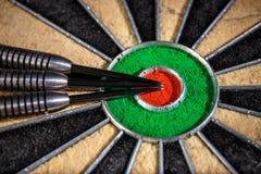 Three darts lying on dartboard. Close up Royalty Free Stock Photos