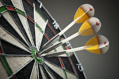 Three darts in the target center Stock Photography