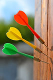 Three darts at wooden board. Red, green and yellow dart stuck in the wooden board Stock Images