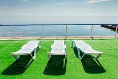 Three deckchairs on beach, facing out to sea Stock Images