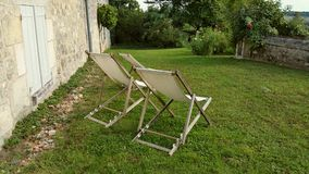 Three canvas deckchairs on lawn. In French country garden with green grass and stone walls Stock Image