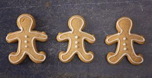 Three Decorated Gingerbread Men on a Dark Surface. A Line of Three Decorated Gingerbread Men on a Dark Surface royalty free stock images