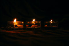 Three decorative candles on dark background. Three decorative candles on dark striped background royalty free stock images