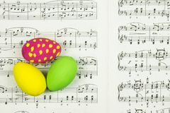 Three decorative painted Easter eggs on sheet with music notes as background. Three decorative painted colorful Easter eggs and page with classic music notes as stock photo