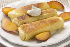 Three Delicious Cheese Blintzes with Sour Cream and Peaches Stock Images