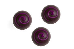 Three delicious chocolate bonbon. Three dark dekorated chocolate bonbons isolated on white background stock images