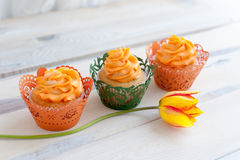 Three delicious cupcakes with orange cream Stock Images