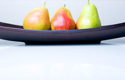 Three delicious fresh colorful pears. In a wooden vase Royalty Free Stock Photos