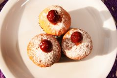 Still life with three delicious cupcakes. Three delicious fresh cupcakes with cherries and powdered sugar on a white plate, close-up Stock Image