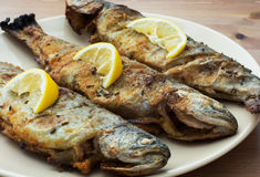 Three delicious grilled trouts. Delicious grilled trout with lemon on the table Stock Photo