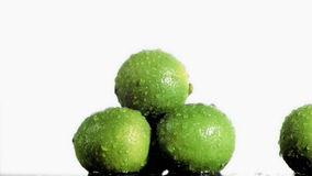 Three delicious limes in super slow motion being soaked stock footage