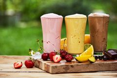 Three delicious milkshakes and smoothies outdoors stock images