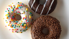 Three delicious sweet donuts rotating on a white plate. Looped. stock footage