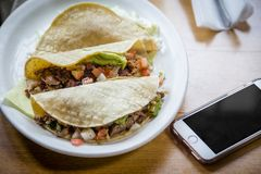 Three tacos on a plate next to a cell phone royalty free stock photo