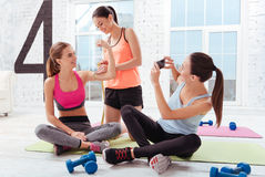 Three delighted women checking their training results in gym Stock Images
