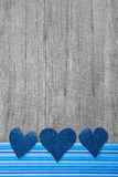 Three denim hearts on wooden shabby background Stock Photos