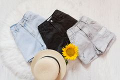 Three denim shorts, straw hat, shorts. On white fur, top view.  Stock Images