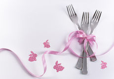 Three dessert forks with pink decoration and bunnies for kid's p. Silverware on white with pink ribbon as background for menu and invitation Stock Images