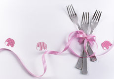 Three dessert forks with pink decoration and elephants for kid's. Silverware on white with pink ribbon as background for menu and invitation Royalty Free Stock Photo