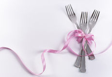 Three dessert forks with pink decoration for kid's party. Silverware on white with pink ribbon as background for menu and invitation Stock Photography