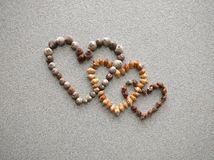 Three diagonal connected hearts created with atlantic snail shells. Collected at the beach of Maspalomas canary islands Royalty Free Stock Photography