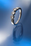 Three diamonds engagement ring. Three briliant cut diamonds set platinum engagement ring Stock Images