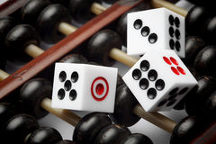 Three dice on abacus are symbolic of gambling Stock Photography
