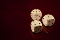 Three dice cubes on dark reflecting wooden background games fortune. Royal flush poker cards combination  casino luck fortune Royalty Free Stock Photos