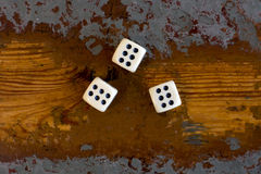 Three dice with number six. On old vintage table Stock Photography