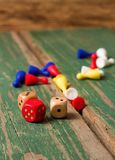 Three dices and color figurines on old wooden board Royalty Free Stock Photography