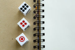 Three dices on notebook. Three dices on blank notebook Stock Photo