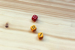 Three dices on wooden background. Three dices red and yellow on wooden background. Dice chance oropportunity concept Stock Images