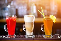 Three different alcoholic cocktails at bar counter stock photos