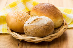 Three different buns in wicker basket on table Stock Images