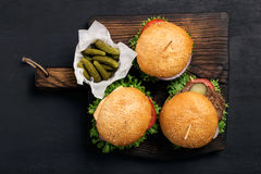 Three different burger on massive wooden board with pickles Royalty Free Stock Photos