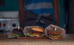 Three Different Burgers Laying On Wooden Counter Stock Photo