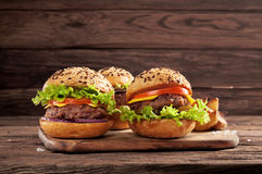 Three different burgers on wooden background Stock Photos