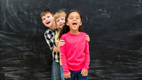 Three different children stand one by one peeking out from behind each other Royalty Free Stock Image