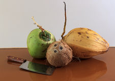 Three different coconuts with machete Stock Images