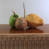 Three different coconuts on table. Three different coconuts on rattan table, old and fresh green and yellow coconuts Royalty Free Stock Photo