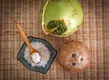 Three different coconuts. Young and old coconuts with bowl full of coconut flakes on rattan table top view Stock Images