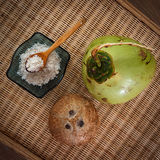 Three different coconuts. Young and old coconuts with bowl full of coconut flakes on table top view Royalty Free Stock Photography