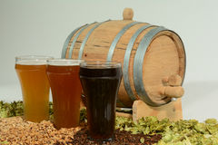 Three different colored beers. Three beers in taster glasses surrounded by various colored grain and hops in front of barrel Stock Photo