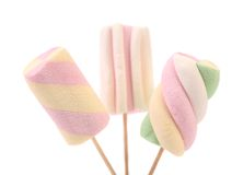 Three different colorful marshmallow on sticks. Stock Photos
