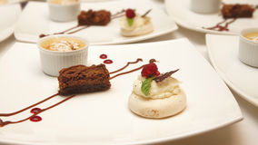 Three different decorated desserts served in white ceramic square plates. On white table Royalty Free Stock Photo