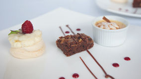 Three different decorated desserts served in white ceramic square plates. On white table Stock Image