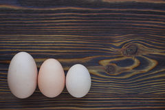 Three different eggs laying on the wooden background can show yo Stock Image