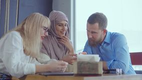 Three different ethnic friends man and women are chatting in cafe in daytime. Blonde woman, her arabic female friend are chatting with handsome man in cafe stock footage