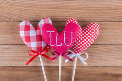 Three different fabric hearts on wooden sticks with ribbon bows placed on a wooden background. Photo Valentines Day Royalty Free Stock Photos
