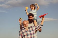 Three different generations ages: grandfather father and child son together. Happy family. Grandfather playtime. Happy